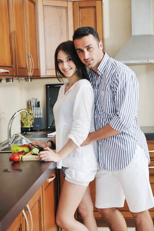 happy young couple have fun in modern wooden  kitchen indoor while preparing fresh food Stock Photo - 9936154