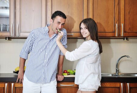happy young couple have fun in modern wooden  kitchen indoor while preparing fresh food Stock Photo - 9936011