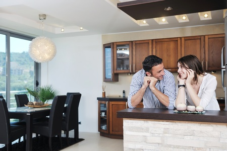 sweet smile: happy young couple have fun in modern wooden  kitchen indoor while preparing fresh food