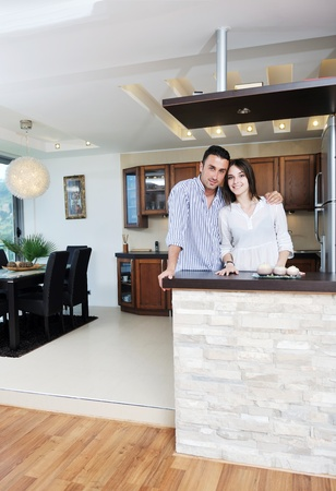 happy young couple have fun in modern wooden  kitchen indoor while preparing fresh food photo