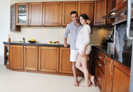 happy young couple have fun in modern wooden  kitchen indoor while preparing fresh food Stock Photo - 13270908