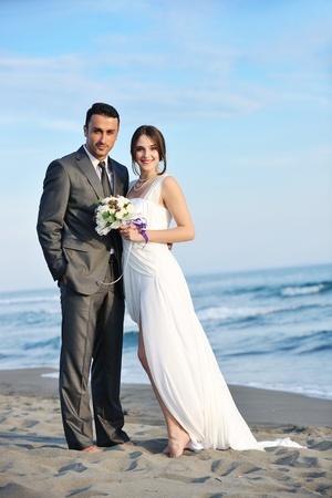 casados: feliz pareja de reci?n casados ??j?venes que celebraban y se divierten en la playa hermosa puesta de sol Foto de archivo
