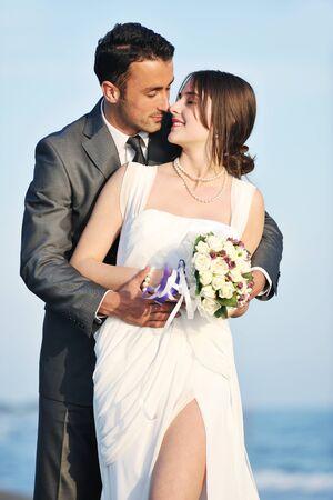 recien casados: feliz pareja de reci�n casados ??joven celebrar y divertirse en el hermoso atardecer en la playa