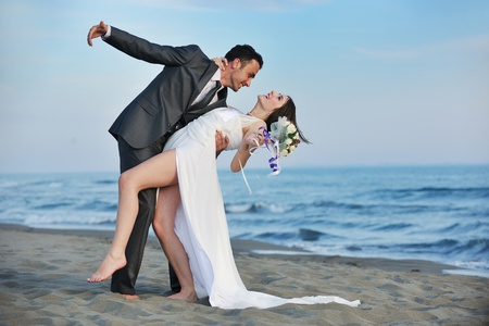 happy just married young couple celebrating and have fun at beautiful beach sunset Stock Photo - 9948116