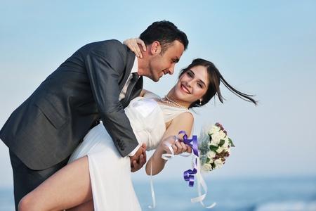 net getrouwd: gelukkig net getrouwd jong stel vieren en plezier hebben op mooi strand zonsondergang