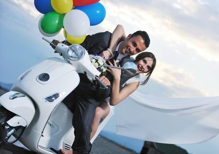 wedding sce of bride and groom just married couple on the beach ride white scooter and have fun photo
