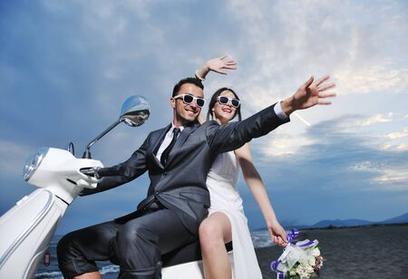 wedding sce of bride and groom just married couple on the beach ride white scooter and have fun Stock Photo - 9901394