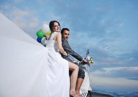 wedding sce of bride and groom just married couple on the beach ride white scooter and have fun Stock Photo - 9901525