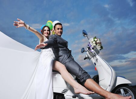 wedding sce of bride and groom just married couple on the beach ride white scooter and have fun Stock Photo - 9901391