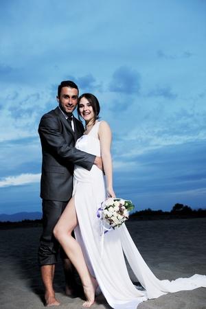 gelukkig net getrouwde jonge koppel vieren en veel plezier bij zonsondergang prachtige strand