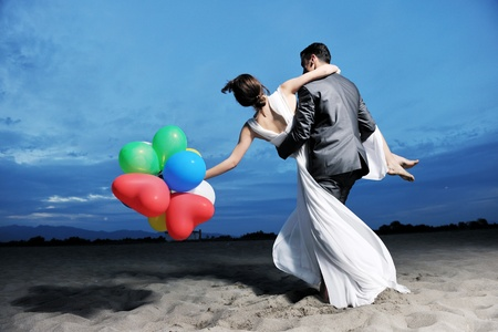 happy just married young couple celebrating and have fun at beautiful beach sunset Foto de archivo