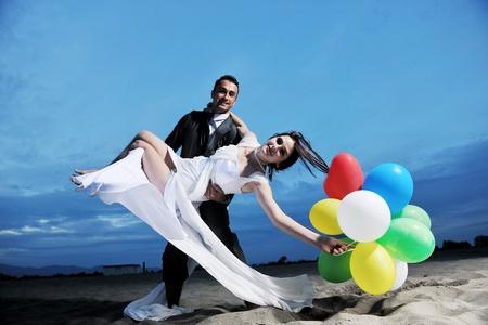 nozze: felice appena sposate giovane coppia festeggiare e divertirsi al tramonto bella spiaggia