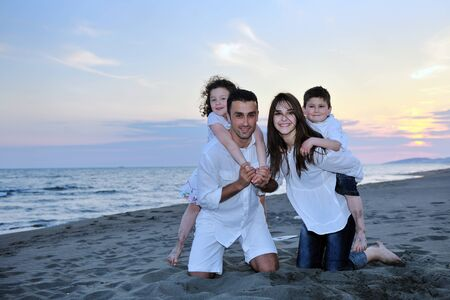 happy young family have fun and live healthy lifestyle on beach photo