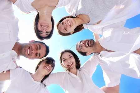 friendship circle: Group of happy young people in circle at beach  have fun and smile