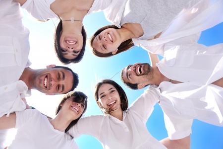 personas: Grupo de j�venes felices en c�rculo en la playa de tener diversi�n y sonrisa