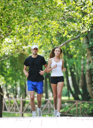 runing: happy young younpe jogging and runing outdoor in nature at sunny day Stock Photo