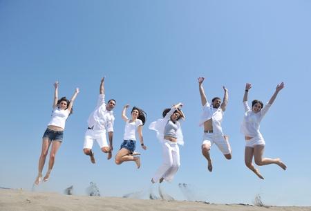 행복 한 사람들 그룹은 해변 아름다운 모래 해변 달리기와 점프가