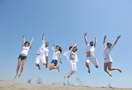 happy people group have fun  run and jump  on beach beautiful sand  beach Stock Photo