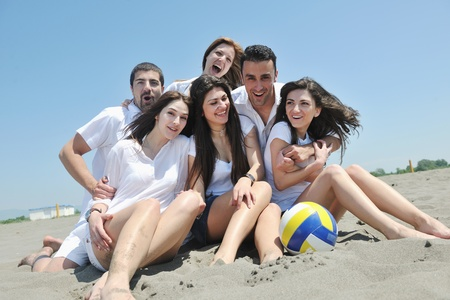 happy young people group have fun  run and jump  on beach beautiful sand  beach photo