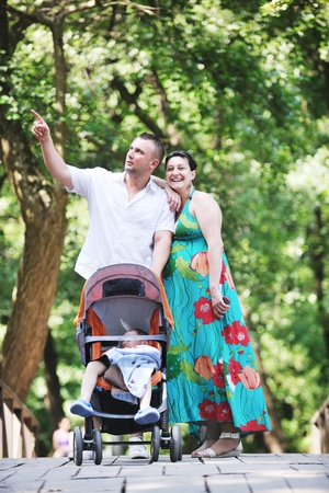Happy young Family at park relaxing and have fun with pregnant woman photo