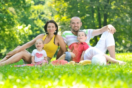 happy young couple with their children have fun at beautiful park outdoor in nature Stock Photo - 10415036