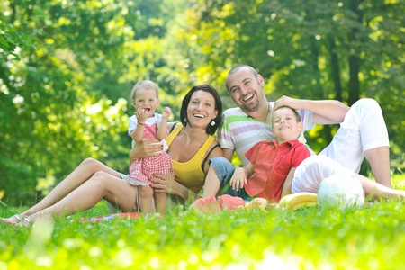 happy young couple with their children have fun at beautiful park outdoor in nature Stock Photo - 10415032