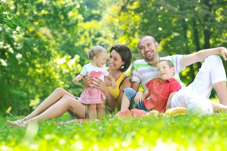 happy young couple with their children have fun at beautiful park outdoor in nature Stock Photo - 10415035