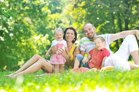 happy young couple with their children have fun at beautiful park outdoor in nature Stock Photo - 10415033