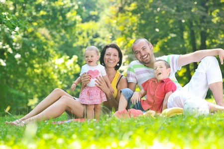 happy young couple with their children have fun at beautiful park outdoor in nature Stock Photo - 10415037