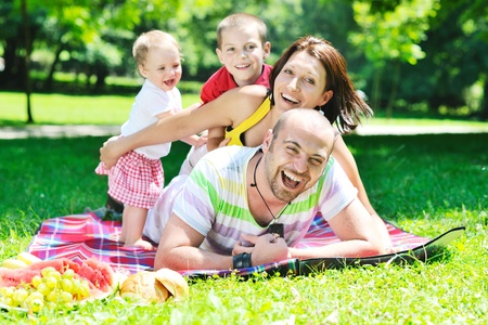picnic: happy young couple with their children have fun at beautiful park outdoor in nature