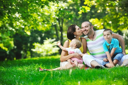 happy young couple with their children have fun at beautiful park outdoor in nature Stock Photo - 10415167