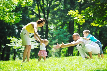 happy young couple with their children have fun at beautiful park outdoor in nature Stock Photo - 10415197