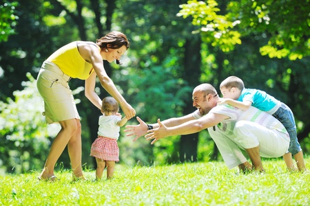 family picnic: happy young couple with their children have fun at beautiful park outdoor in nature