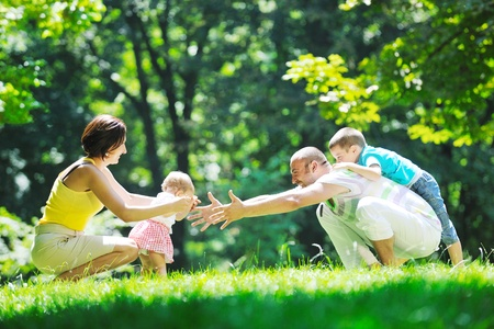 happy young couple with their children have fun at beautiful park outdoor in nature Stock Photo - 10415246