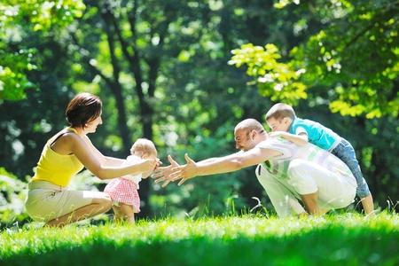 padres e hijos felices: parejita feliz con sus hijos divertirse en el hermoso parque al aire libre en la naturaleza