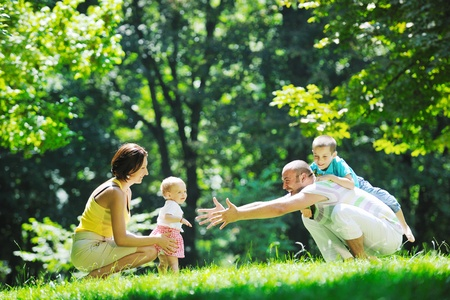 happy young couple with their children have fun at beautiful park outdoor in nature Stock Photo - 10415231