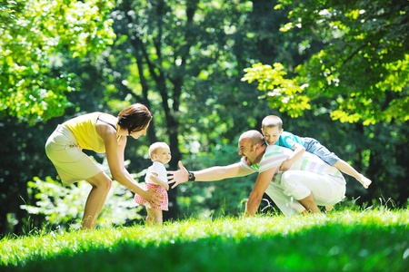 fun woman: happy young couple with their children have fun at beautiful park outdoor in nature