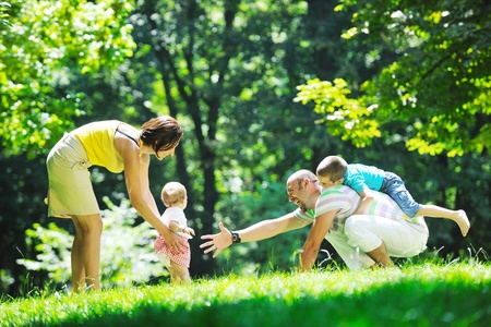 happy family nature: happy young couple with their children have fun at beautiful park outdoor in nature