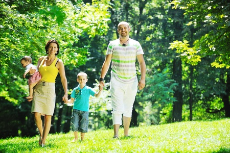mother nature: happy young couple with their children have fun at beautiful park outdoor in nature