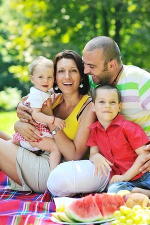 family picnic: parejita feliz con sus hijos divertirse en el hermoso parque al aire libre en la naturaleza