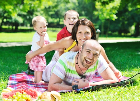 happy young couple with their children have fun at beautiful park outdoor in nature Stock Photo - 10439489