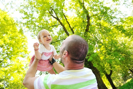 happy family man and baby children playing in bright park while representing happines and parenthood concept photo