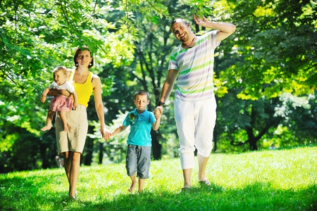happy young couple with their children have fun at beautiful park outdoor in nature Stock Photo - 10439476