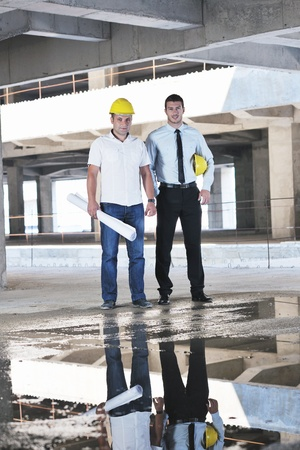 job site: Team of business people in group, architect and engeneer  on construciton site check documents and business workflow on new building