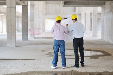 architecture plans: Team of architects people in group  on construciton site check documents and business workflow Stock Photo
