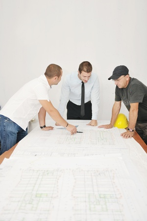 Team of architects people in group  on construciton site check documents and business workflow photo