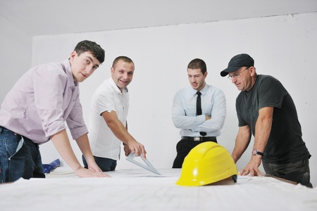 contractors: Team of architects people in group  on construciton site check documents and business workflow Stock Photo