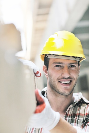 manual job: handsome hard worker people portrait at concstruction site Stock Photo