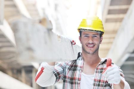 constructor: Retrato de pueblo trabajador guapo en el sitio de concstuction