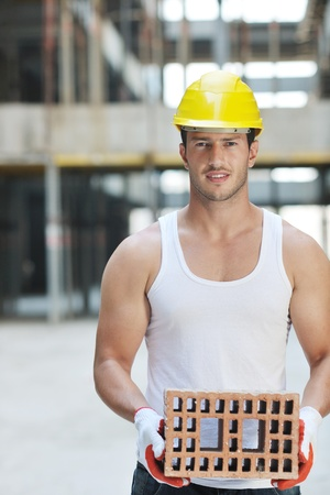 yellow hard hat: handsome hard worker people portrait at concstruction site Stock Photo